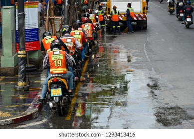 BANGKOK, THAILAND - 15 DEC : Motorcycle taxi queue up and District staff worker cleaning footpath on 15 December 2018 in Silon road, Bangkok, Thailand