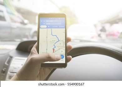 BANGKOK, THAILAND - 15 DECEMBER 2016: Close up of man holding Samsung smartphone and using application Google Maps to destination. navigation service by Google company