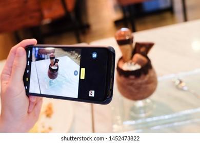 Bangkok, Thailand : 15 June 2019, The hand holding the mobile phone taking the photo of chocolate cream dessert