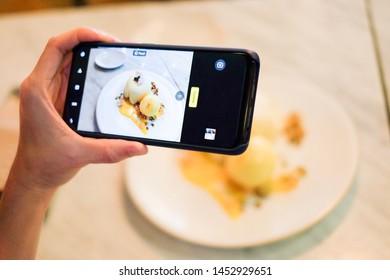 Bangkok, Thailand: 15 June 2019 - The hand holding the mobile phone taking the photo of ice cream dessert