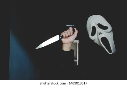 "BANGKOK, THAILAND, 16 AUG 2019 - Scary Halloween Ghost making a horror facial expression, The figure of the killer maniac with a knife from the movie ""Scream"""