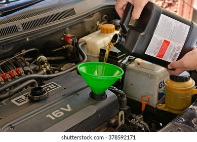 Bangkok, Thailand - 16 Dec 2015: A refiling motor oil(Amsoil Signature 5w30 Fully Synthetic) in the car engine(Chevrolet Aveo)