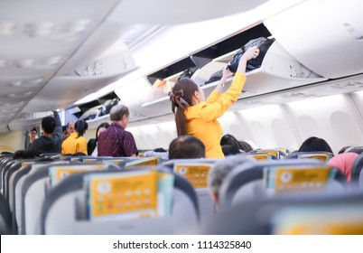 Bangkok, Thailand, 17 June 2018 Air hostess Friendly flight attendant helping passenger to put luggage cabin compartment. To the passengers on the plane.Blur softfocus.