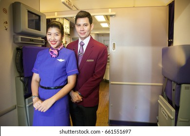 Bangkok Thailand 18 jun 2017 : Cabin crew in purple uniform of Thai airways was standing in front of the aircraft entrance and welcome passenger to the aircraft.