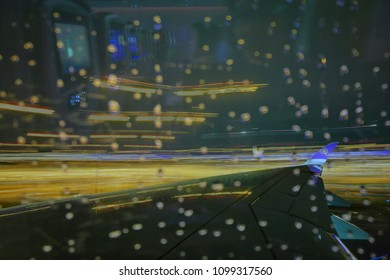 Bangkok Thailand 18 may, 2018. Thai airways aircraft wing moving during take off in a rainy weather night. water droplets on windows glass. light trail movement in the background
