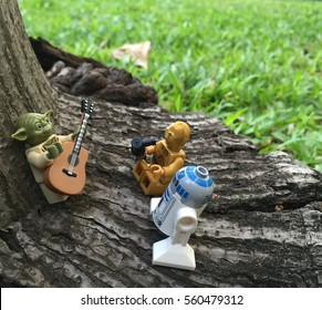 Bangkok, Thailand: 20 Jan 2017 - Lego Yoda playing music in the park with C3-PO and R2-D2. These mini figures are from Star Wars sets. Lego is a brick brand by Lego group.