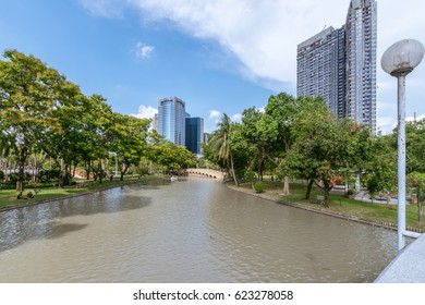 BANGKOK, THAILAND - 2017 April 09 : Sunny spring green nature park outdoor with canal in summer and nice weather at Chatuchak park