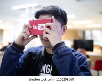 Bangkok , Thailand 2018 Developer testing Youtube Virtural Reality Device cardboard with two hand holding inside office space
