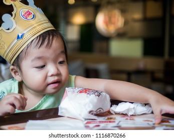 BANGKOK THAILAND, 2018: Little girl with a cardboard crown at Burger King restaurant. Burger King is an American global chain of hamburger fast food restaurants.