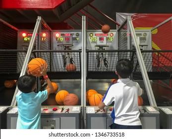 Bangkok, Thailand. 20th March 2019. Asian brothers enjoying basketball hoop shooting game inside Game Center in Bangkok. Selected focus.