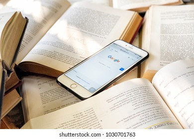 "Bangkok, Thailand - 21 February:  The most popular internet search engine on these days ""Google Web Browser"" on a smartphone which is surrounded by pile of books in a library"