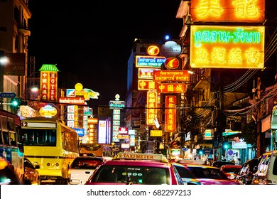 BANGKOK, THAILAND - 21 July, 2017: Cars and transports drive on Yaowarat road at the street of Chinatown. with the signage and advertisement shop and restaurant lighting background in the night shot.