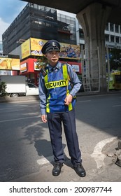 BANGKOK, THAILAND - 21 NOV 2013: Unidentified security man in uniform stands on street and controls passage to office building.