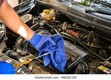 BANGKOK, THAILAND - 22 JUNE 2016 : Mechanic checking the motor oil level  in the car engine(Chevrolet Aveo1.6)