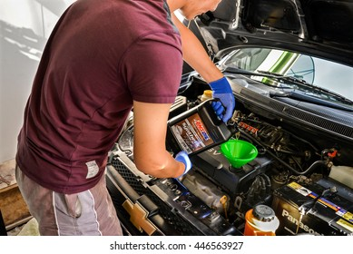 BANGKOK, THAILAND - 22 JUNE 2016: A refiling motor oil(Amsoil Signature 0w30 Fully Synthetic) in the car engine(Chevrolet Aveo1.6)