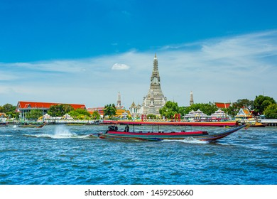 Bangkok, Thailand 22 June 2019:View over river Chao Phraya from boat back to temple Wat Arun, eldest temple in Bangkok. In foreground is speed longboat passing. Behind are tour boats and ferries.