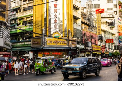 Bangkok, Thailand - 25 February, 2017: People, Motorbikes and Tuk-Tuks on the Yarowat Road, also known as Chinatown, in the late afternoon