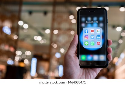 BANGKOK, THAILAND- 26 June 2019 : Hands of man use Iphone with social media application of facebook, youtube, google search, instagram, twitter, linked in, line whatsapp, and pinterest on black backgr