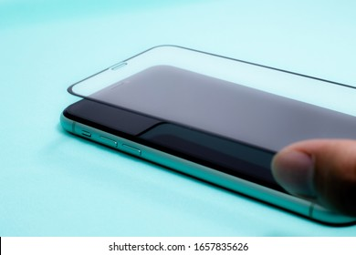 Bangkok, Thailand - 27  February 2020: change the screen protective glass of Apple launch new smartphone iPhone 11 on light blue fabric background