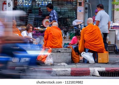 "Bangkok, Thailand - 27 Jun 2018: In the morning, Buddhist offer food to the monks in Thais call ""Tak Bat"". Giving alms to monks is showing goodness to others and doing good deeds. Blurred motorcycle"