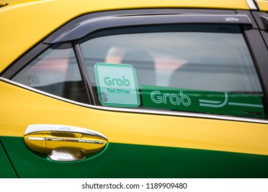 BANGKOK, THAILAND - 27 MARCH, 2018: Grab branded taxi cab on the street of Bangkok, Thailand.
