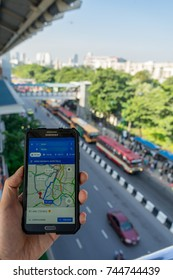 BANGKOK, THAILAND - 27 OCTOBER 2017: Close up of man holding Samsung smartphone and using application Google Maps to destination at bus station background. navigation service by Google company