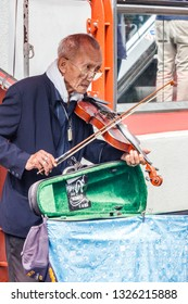 Bangkok, Thailand - 27th March 2018: Old man with violin busking for money. Pensions are very small if at all.