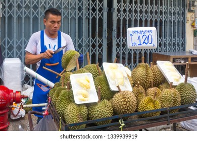 Bangkok, Thailand - 2nd August 2017: Durian vendor preparing durian fruit for sale, street market. Durian is famous for its pungent smell.