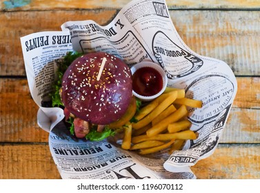Bangkok, Thailand - 3 July 2017 : Top view Bacon Hamburger and french fries with tomato sauce wrapped with paper on the wooden table