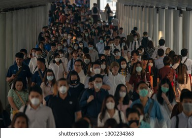 BANGKOK THAILAND, 30 Jan 2019 :Group of many salary man wearing face mask for protect micro dust in air while going to their workplace during pm2.5 air pollution crisis in Bangkok at moring rush hour.