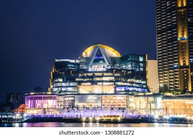 BANGKOK, THAILAND - 30 Jan, 2019: Exterior view of ICON Siam at River side. ICON SIAM is the new Shopping Center and Landmark of Bangkok at night with motion blur of many tourist in front.
