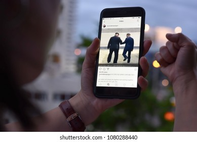 BANGKOK, THAILAND- 30th April 2018 :Hands of woman with joy watching video clip of Kim Jong-un, north korean leader shaking hands with Moon Jae-in, president of south korea via Instagram application