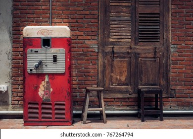 Bangkok, Thailand, 4 June 2017: vintage machine cabinet of Coca Cola brand  with the red brick wall, is a carbonated soft drink produced by The Coca-Cola Company