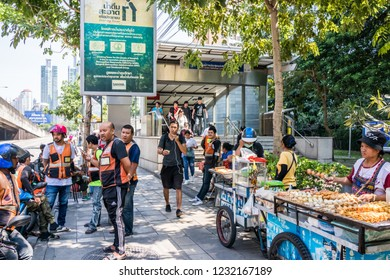 Bangkok, Thailand - 4th October 2018: Motorcycle taxis and street food vendors wait for customers by the entrance to the MRT. The underground system is currently being expanded.