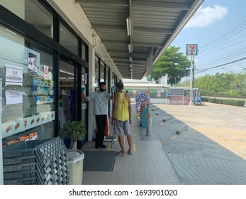 Bangkok, Thailand - 5 April 2020: supermarket staff holding infrared thermometer to measuring temperature of the customer before enter store.