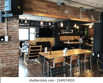 Bangkok, Thailand; 5 August 2018: Modern cafe interior with a brick wall, a wooden tables, white sofas. The interior design of a Coffee shop, cafe.