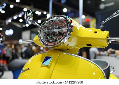BANGKOK, THAILAND - 6 APR 2019: Close up front view detail of elegantly designed vespa scooter display in exhibition hall. Vespa is an Italian brand of scooter manufactured by Piaggio.