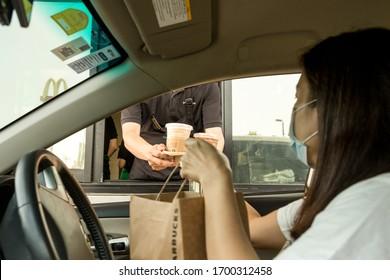 Bangkok Thailand 6 Apr 2020 - At Starbucks staff serving coffee to customer at drive thru counter during coronavirus outbreak.