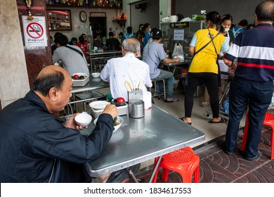 Bangkok, Thailand - 8/14/20: A man enjoys his soup as other customers que to buy their lunch in a Chinatown eatery popular with locals and tourists.