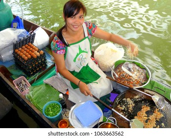 BANGKOK, THAILAND - APR 10, 2010: Young female Thai boat vendor sells fried oyster omelettes from her boat at Taling Chan Floating Market, on April 10, 2010.