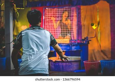 Bangkok, Thailand - Apr 11 2019 : A man play dunk tank girl game at night market.