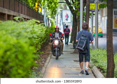 BANGKOK, THAILAND - APR 15 : Motorbike is running on footpath in Bangkok on April 15, 2019. It is one of traffic problems in Bangkok.