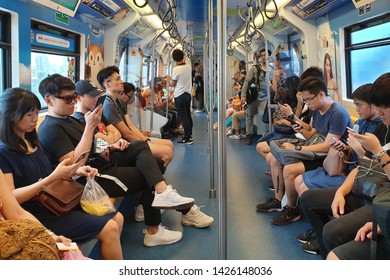 BANGKOK, THAILAND - APR 7, 2019: Passengers using mobile device in Bangkok mass Transit System (BTS) train.