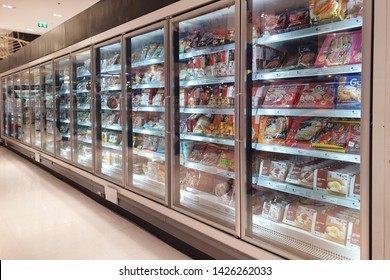BANGKOK, THAILAND - APR 7, 2019: Interior view of huge glass freezer with various brand frozen foods in Siam Paragon grocery store. It is one of the largest shopping malls in Thailand.