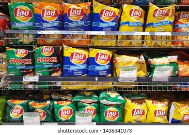 BANGKOK, THAILAND - APR 7, 2019: Various flavoured of lay's potato chips display on store shelf in Siam Paragon Mall. Lay's has been owned by PepsiCo through Frito-Lay since 1965.