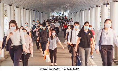Bangkok, Thailand - Apr 7, 2020: Crowded Asian people wear face mask walking in pedestrian walkway. Coronavirus disease Covid-19 pandemic outbreak effect on human, city life, or air pollution concept