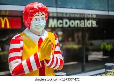 Bangkok ,Thailand - April 01 2020 : Mr.Ronald McDonald or McDonald clown mascot wearing a Hygienic mask and waiting for customer because of Covid-19 or Coronavirus crisis, Illustrative Editorial