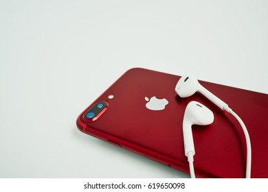 BANGKOK, THAILAND - April 08, 2017: Side view of New iPhone 7 Plus  and EarPods, Special Edition in RED color Apple product on white background