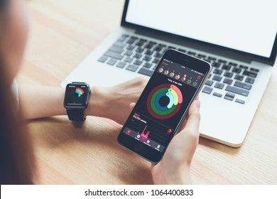 Bangkok, Thailand - April 09, 2018 : Women using the phone and checking activity app on Apple Watch, Created and developed by the Apple inc.