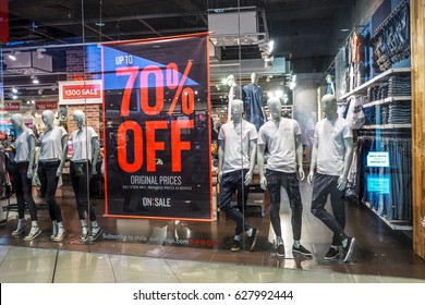 BANGKOK THAILAND, April 1, 2017: Large red Sale letters on a glass wall obstruct a view inside the popular clothing cotton on store. Sale 70% Off & Over - Final Sale at ikea bangna Thailand.